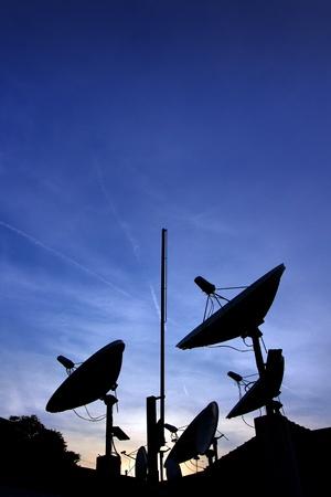 antena parabolica: Platos satelitales siluetas en el techo sobre la puesta de sol. Foto de archivo