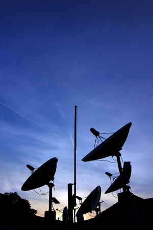 Satelite dishes silhouettes  on the roof over sunset. Standard-Bild