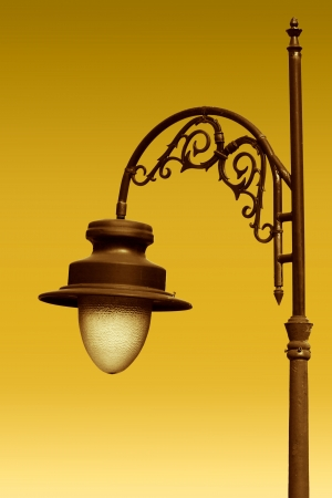 outdoor lighting: Aged gilded street lamp over yellow background