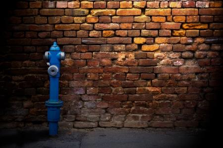 borne fontaine: Bouche d'incendie contre un mur de brique dans une rue de côté Banque d'images