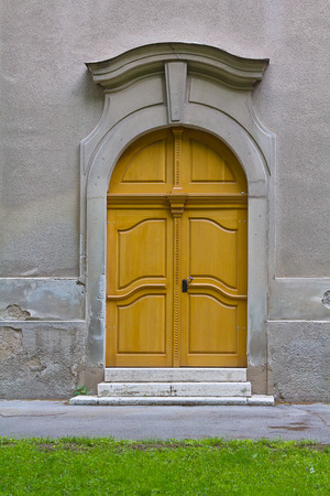 backdoor: Yellow side door on the old church wall    Stock Photo