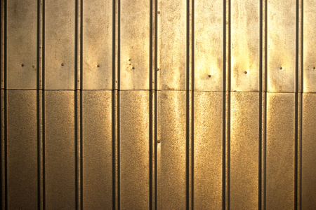 sheeting: shiny metal surface illuminated by sunlight.