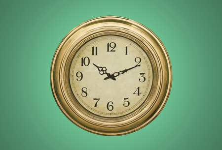 green house effect: Rustic clock isolated over the green background