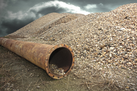 orifice: Rusty industrial  drain pipe next to a pile of gravel. Stock Photo