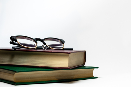 Stack of books isolated on white with glasses