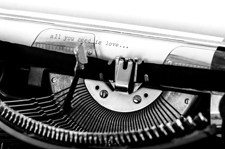 sentence typescript: Close up of a typewriter with the All you need is love text typed on a white paper. Stock Photo