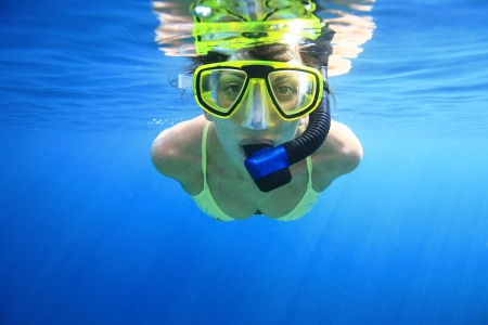 Woman snorkeling in the blue Imagens