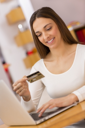 paying money: Female holding a  charge card and shopping from the web on laptop