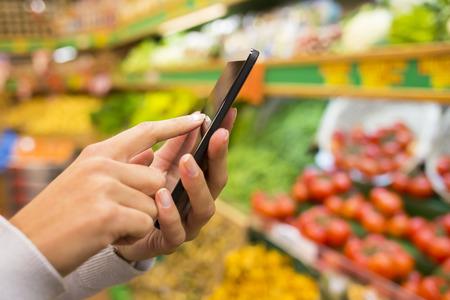 tiendas de comida: Mujer colse-up store mano del teléfono celular Foto de archivo