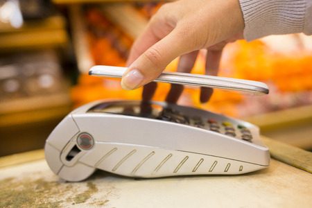 rfid: Female electronic payment close-up cell phone hand shop electronic reader Stock Photo