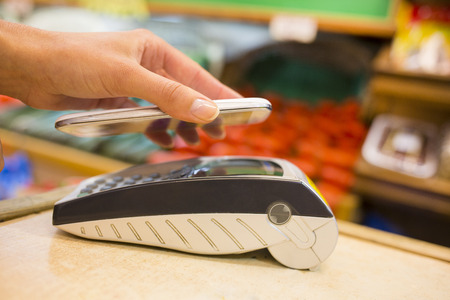 wireless terminals: Female electronic payment close-up cell phone hand shop electronic reader Stock Photo