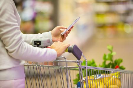 telefonok: Nő áruházi mobiltelefon közeli Stock fotó