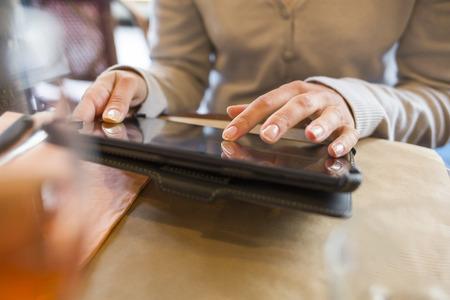 女性のデジタル タブレット コンピューター バー レストラン 写真素材