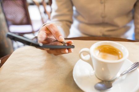 女性のスマート フォンのコーヒーバー sms メール