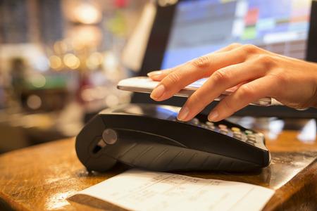 Vrouw elektronisch betalen close-up mobiele telefoon hands winkel elektronische reader Stockfoto