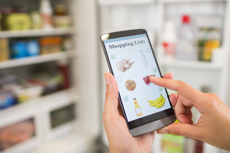 Woman Makes shopping list on mobile phone connected to the refrigerator Standard-Bild