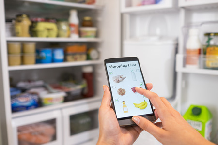 retail business: Woman Makes shopping list on mobile phone connected to the refrigerator Stock Photo