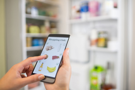 Woman Makes shopping list on mobile phone connected to the refrigerator Stock Photo