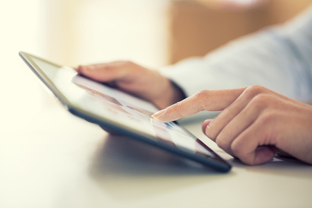 Woman using digital tablet indoor Standard-Bild