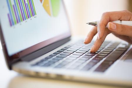 teclado de computadora: Mujer que trabaja en los datos financieros con la computadora Foto de archivo