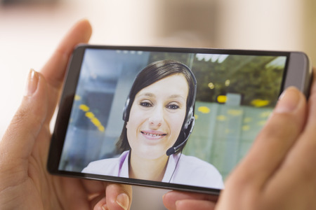 Closeup of a female hand holding a smart phone DURING a skype video photo