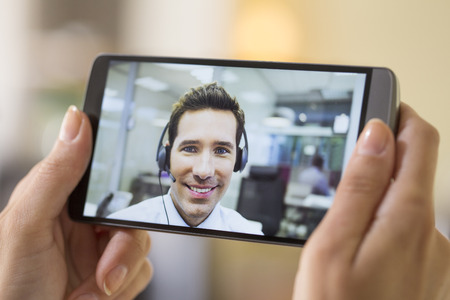video conference: Closeup of a female hand holding a smart phone DURING a skype video Stock Photo