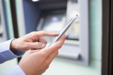 Woman using her mobile phone in front of a cash machine