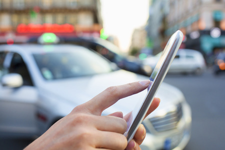 hailing: Woman orders a taxi from her mobile phone