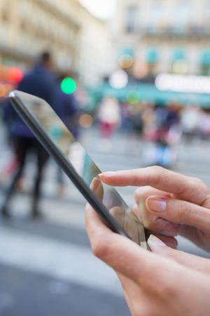 携帯電話を使用してパリの路上で女性