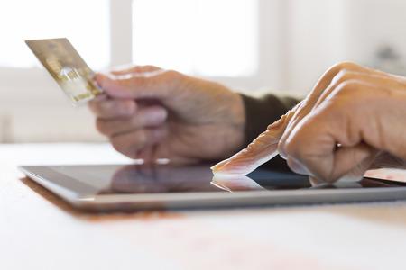 Mature female digital tablet closeup hands plastic card shop indoors photo
