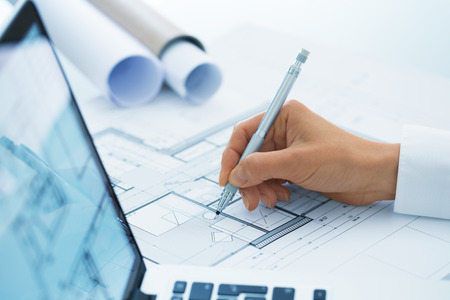 architect office: Woman Architect drawing on print  construction project