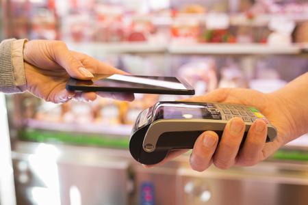 女性の携帯電話、スーパー マーケットの肉屋で NFC 技術で支払い