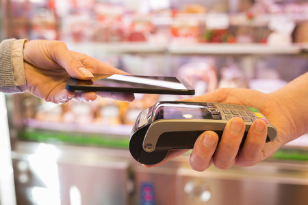 Woman paying with NFC technology on mobile phone, in supermarket butcher
