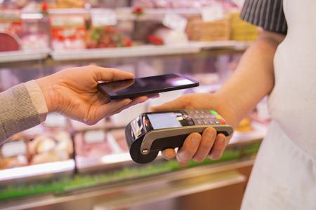 Vrouw te betalen met NFC-technologie op de mobiele telefoon, in de supermarkt slager Stockfoto