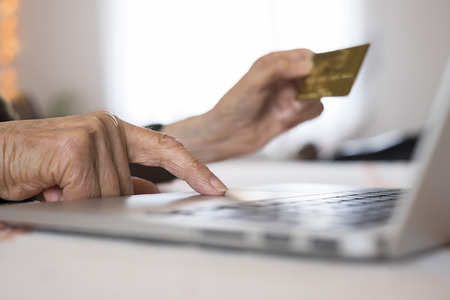 Senior Woman Using Computer and  credit card, shopping online photo