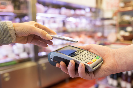 Woman paying with NFC technology on mobile phone, in supermarket Standard-Bild