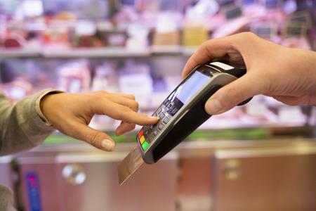 tarjeta de credito: Mano de la mujer con el golpe de tarjeta de cr�dito a trav�s de terminales para la venta, en el mercado