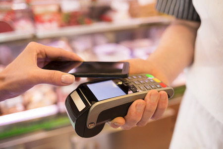 Woman paying with NFC technology on mobile phone, in supermarket Stock Photo