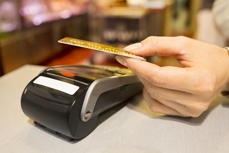 女性 NFC 技術のスーパーでクレジット カードで支払い