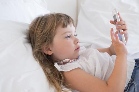 niños jugando videojuegos: Niña linda que usa el teléfono móvil en el hogar Foto de archivo