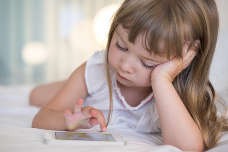 kids playing video games: Pretty Little girl using mobile phone at home