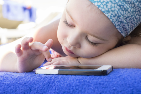 Cute Little girl using mobile phone at home