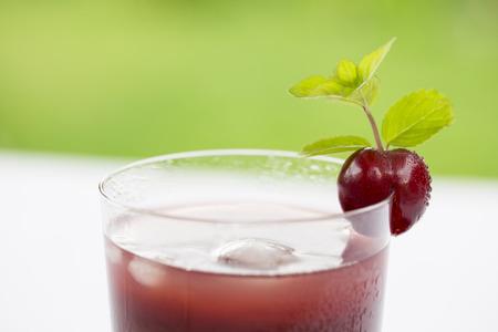 Glass of Cold cherries juice in garden Imagens