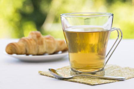 Croissant and hot Tea in garden Imagens