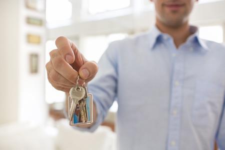 Man thuis sleutels lachend de hand