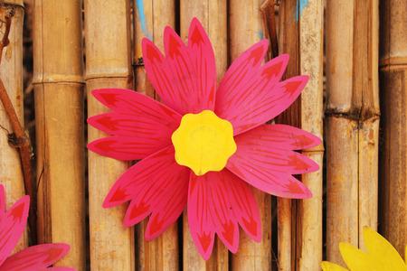A windmill shaped like a flower on a bamboo fence Stock Photo