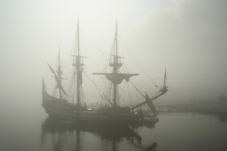 schooner: Old sail ship (Pirate?) in the fog early morning Stock Photo
