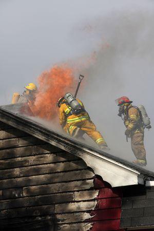 Verlaten huis in vlam met brandweerlieden in actie