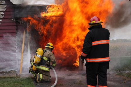 conflagration: Abandoned house in flame with firefighters in action