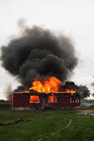 house on fire: Casa abandonada en las llamas con los bomberos en acci�n